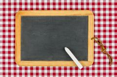 empty blackboard with chalk on a red checkered table cloth - stock photo
