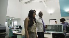 Businessman and businesswoman talking together as they walk around the office Stock Footage