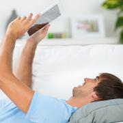 relaxed man reading an ebook - stock photo