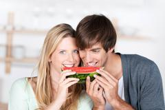 Couple eating melon together Stock Photos
