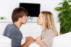 Stock Photo of amorous couple kissing on sofa