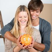 couple between transport boxes holding piggybank - stock photo