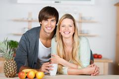 smiling couple in the kitchen - stock photo