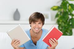 smiling man showing book and ebook - stock photo