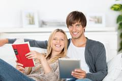 Laughing couple reading book and ebook Stock Photos
