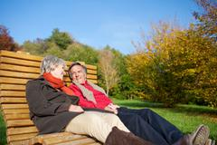 senior couple relaxing in the autumn sun - stock photo