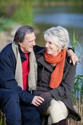 Smiling elderly couple on a lake shore Stock Photos