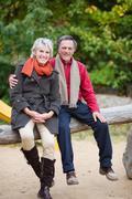 a senior couple sitting on a tree trunk - stock photo