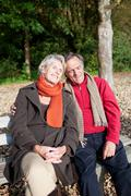Happy tender senior couple sitting on a bench Stock Photos