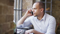 Attractive young man talking on the phone in soft natural light - stock footage