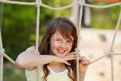 girl leaning on rope at playground - stock photo