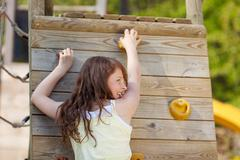 young girl climbing wall at playground - stock photo