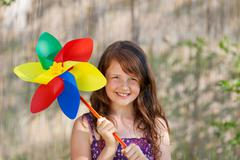 Girl holding colorful pinwheel in park Stock Photos