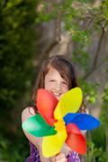 Smiling girl holding windmill in the garden Stock Photos