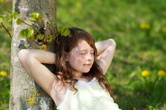 girl with eyes closed leaning on tree trunk in park - stock photo