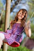 young girl swinging in park - stock photo