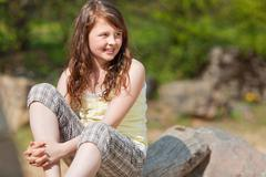 girl looking away while sitting in park - stock photo
