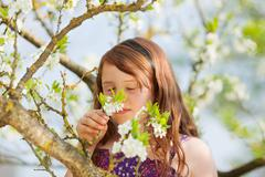little girl smelling blossom - stock photo