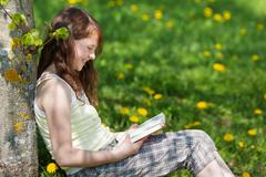 girl leaning on tree trunk while reading book in park - stock photo