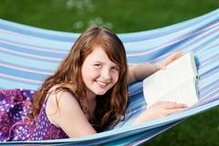 girl with book lying on hammock in park - stock photo