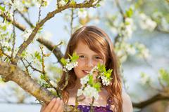 Pretty girl sitting in a tree with blossom Stock Photos