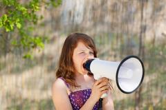 Girl shouting in megaphone Stock Photos