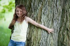 Little girl leaning on tall oak Stock Photos