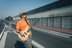 young musician playing bass guitar - stock photo