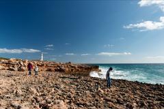 Familiy walking by a stony beach Stock Photos