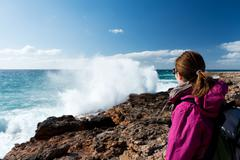 Female backpacker looking at wave splashing on rock Stock Photos