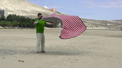 Young man with blanket after picnic on the beach, slow motion shot at 240fps Stock Footage