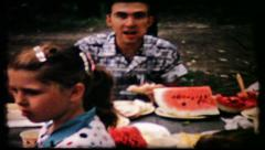 170 watermelon on picnic table at family gathering - vintage film home movie Stock Footage
