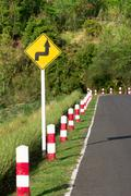 A road sign warns of a sharp turn on a narrow road Stock Photos
