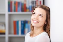 Young woman standing in front of bookshelf smiling Stock Photos