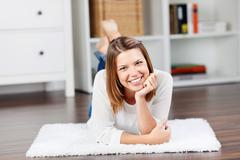 Smiling young woman lying on the floor and posing Stock Photos