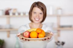 beautiful woman with a plate of fruits - stock photo