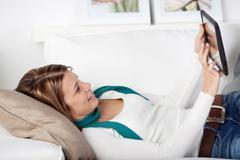 Woman using a tablet-pc on the sofa Stock Photos