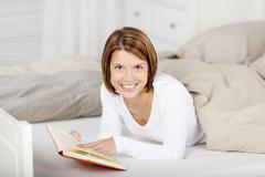 woman giving a smile while reading a book in bed - stock photo