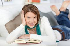 Smiling woman relaxing with a book Stock Photos