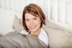 portrait of a woman lying with blanket in bed - stock photo