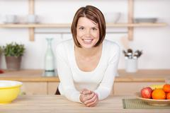 profile portrait of a smiling woman in kitchen - stock photo