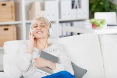 smiling woman enjoying music - stock photo