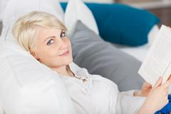 Woman relaxing on sofa with a book Stock Photos