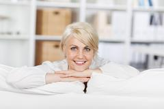 Smiling young woman leaning on sofa Stock Photos