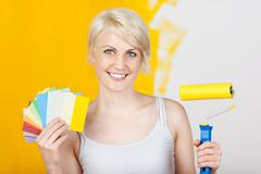 Happy woman holding out color samples and paint roller Stock Photos