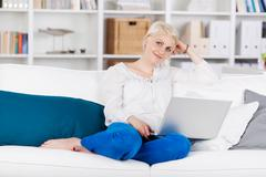 Relaxed woman sitting with laptop on sofa Stock Photos
