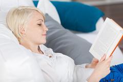 Young woman reading book on sofa Stock Photos