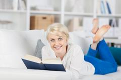 young woman reading book on sofa - stock photo
