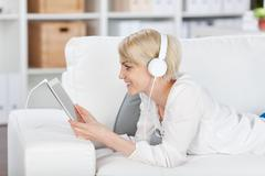 Woman listening music with headphones and tablet at home Stock Photos