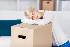 Stock Photo of woman resting head on cardboard box at home